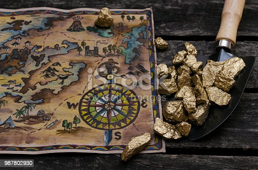 Treasure map and shovel full of gold nuggets ore on wooden table. Treasure hunter or gold miner concept.