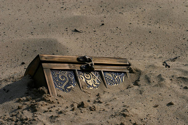 Treasure Chest Treasure chest buried in the sand antiquities stock pictures, royalty-free photos & images