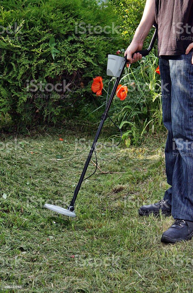 Man exploration treasures in the garden using a metal detector