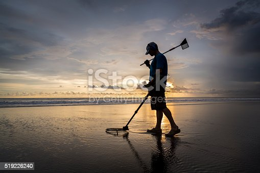 istock Treasure hunter on the beach with a metal detector 519226240