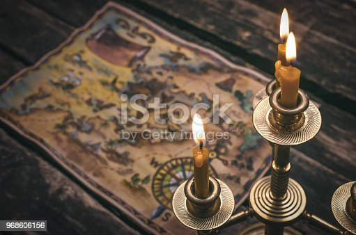 Pirate treasure map and burning candle on aged wooden table background. Treasure hunt concept. Sea travel.