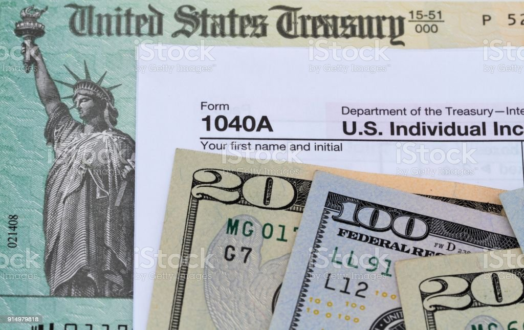 Treasury check and currency with a 1040A tax return form Treasury check and USA currency with a 1040A tax return form 1040 Tax Form Stock Photo