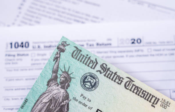 US Treasury check for stimulus in 2020 against a USA Form 1040 US Treasury stimulus check laying on a form 1040 tax return for 2020 to illustrate questions about qualification for payment stimulus check stock pictures, royalty-free photos & images