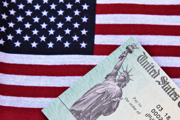 Treasury check on top of American flag - corona virus relief stock photo