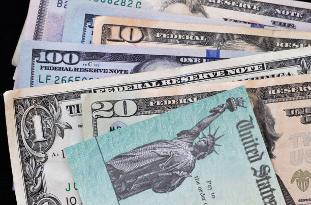 Treasury check on top of various currency bills - corona virus relief A Federal treasury check on top of an assortment of various US currency bills.  Concept image for  government payments for corona virus relief, IRS refund, small business administration loans and grants, or other financial payments. bailout stock pictures, royalty-free photos & images