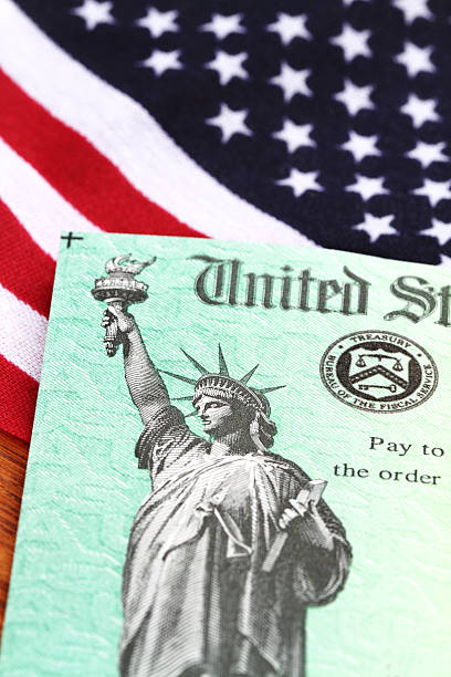 usa treasury irs refund check on american flag - social security check stock photos and pictures