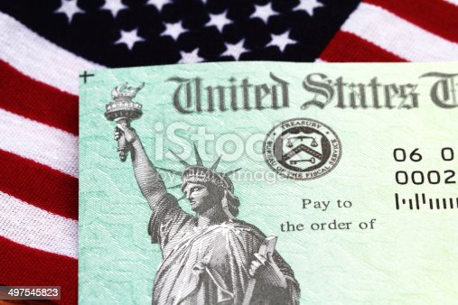 Partial view of a USA Treasury Internal Revenue Service tax refund check showing the Treasury seal and image of the Statue of Liberty. The check is on top of a small USA flag. Treasury checks are also used to pay Social Security and Medicare benefits. Concept of government payments, refunds, welfare or subsidy.