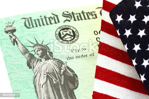 Partial view of a USA Treasury Internal Revenue Service (IRS) tax refund check showing the Treasury seal and image of the Statue of Liberty. The check is under a small folded USA flag. Treasury checks are also used to pay Social Security and Medicare benefits. Concept of government payments, refunds, welfare or subsidy.