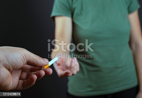 treat with a cigarette. the guy is sharing gives girl on a dark background. harm from smoking.