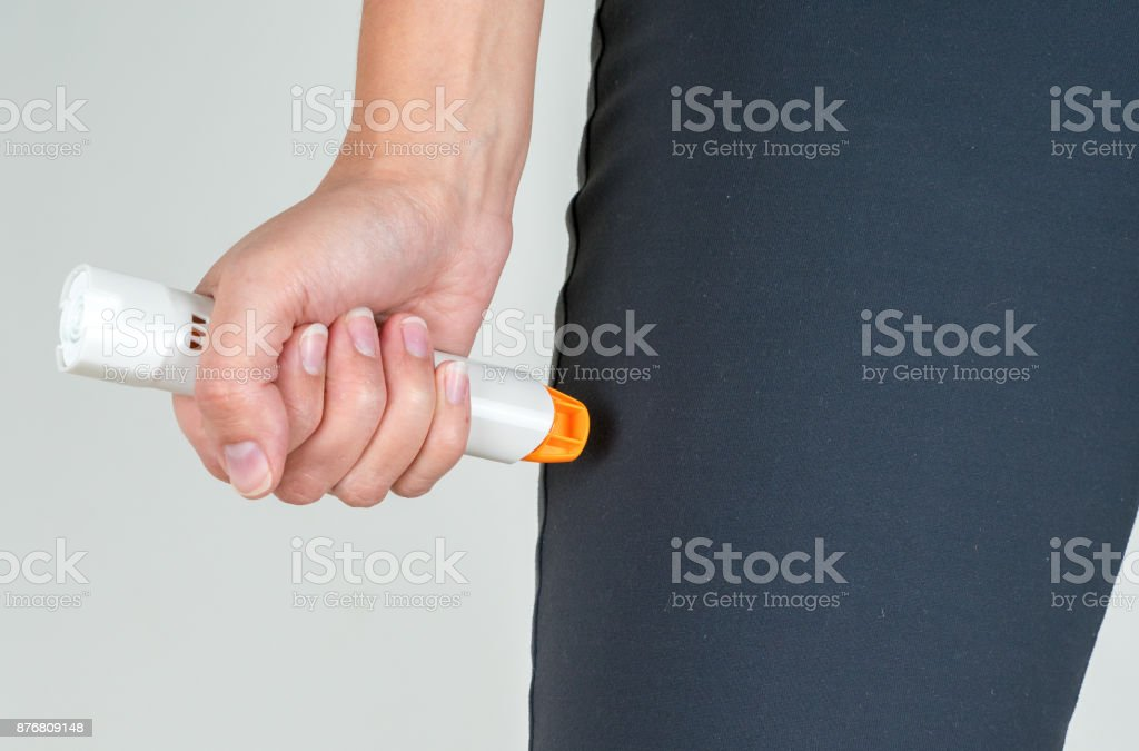 Treating the allergic reaction with the epinephrine stock photo