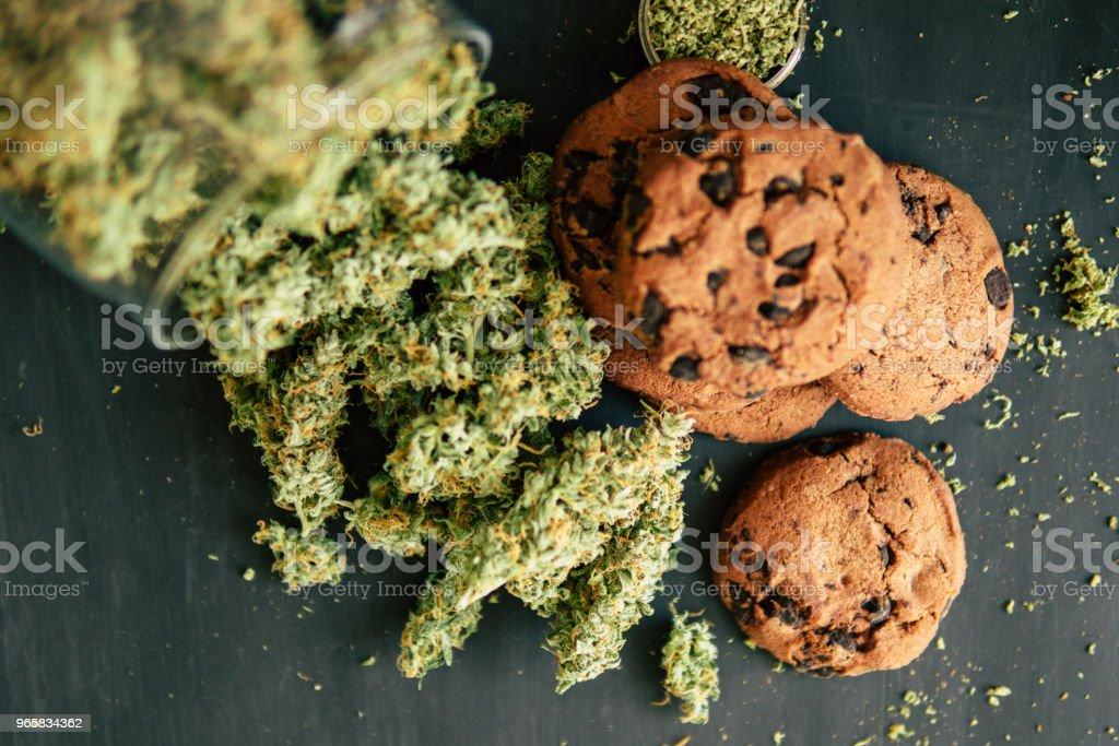 Behandeling van medische marihuana voor gebruik in levensmiddelen, op een zwarte achtergrond. Koekjes met cannabis en toppen van marihuana op de tafel. Kopieer het Concept van de ruimte van het koken met cannabis kruid. - Royalty-free Blad Stockfoto