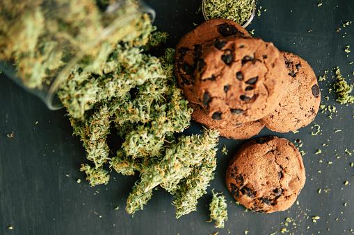 Behandeling Van Medische Marihuana Voor Gebruik In Levensmiddelen Op Een Zwarte Achtergrond Koekjes Met Cannabis En Toppen Van Marihuana Op De Tafel Kopieer Het Concept Van De Ruimte Van Het Koken Met Cannabis Kruid Stockfoto en meer beelden van Blad