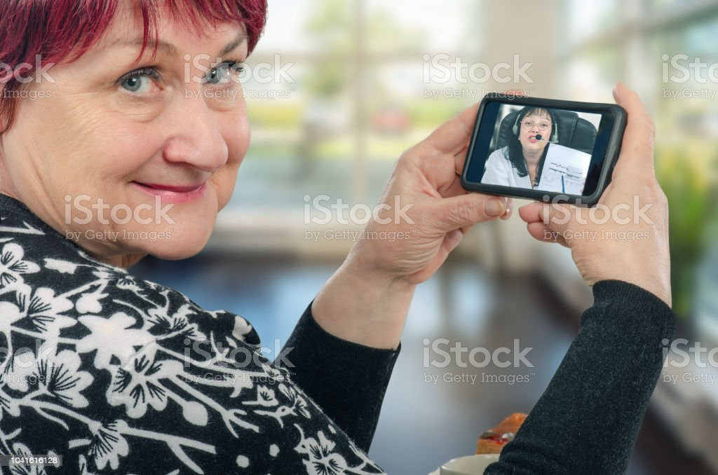 Mature caucasian woman enjoys telecommunication with virtual doctor
