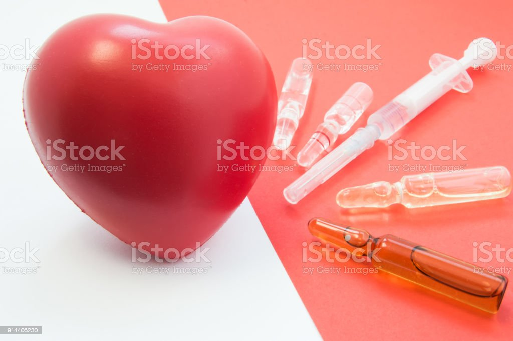 Treatment, support with medication and heart protection. Drugs - vials and syringe on red background aimed at heart, which lies nearby. For use in cardiology and treatment of cardiovascular system stock photo