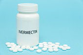 istock Treatments for Coronavirus (COVID-19): IVERMECTIN in white bottle packaging with scattered pills. Isolated on blue background. Horizontal shot. Copy space 1257979917
