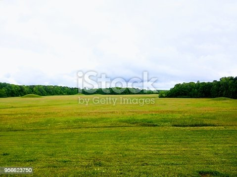 Green grass, mounds and trees line the landscape with dense clouds over top.