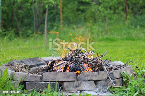 Tree branches burn in a bonfire in a round brick fireplace