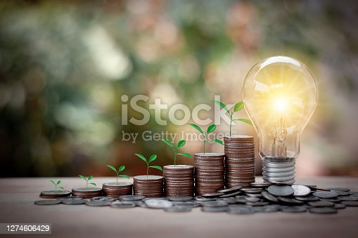The tree are growing on stacks of coins and Energy saving light bulb with bokeh background. Saving money, accounting and financial concept.