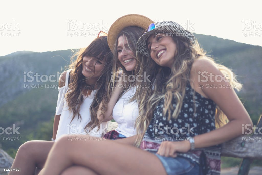 Tree happy girlfriends on bench in nature stock photo
