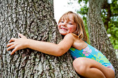 Five year old girl hugging a large tree in a park.
