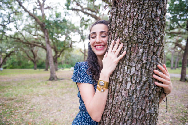 Tree Hugging Millennial Woman Outdoors in Miami Park USA This is a color photograph of a young Millennial woman in her 20's outdoors in a Miami park. She is a Jewish American of Israeli descent. She smiles with her eyes closed as she hugs a tree. tree hugging stock pictures, royalty-free photos & images