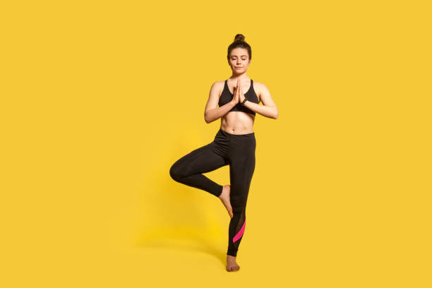Tree pose. Athletic slim woman with hair bun in tight sportswear practicing yoga, doing Vrksasana exercise Tree pose. Athletic slim woman with hair bun in tight sportswear practicing yoga, doing Vrksasana exercise on one leg, hands in prayer namaste gesture. full length studio shot, sport workouts isolated yogi stock pictures, royalty-free photos & images