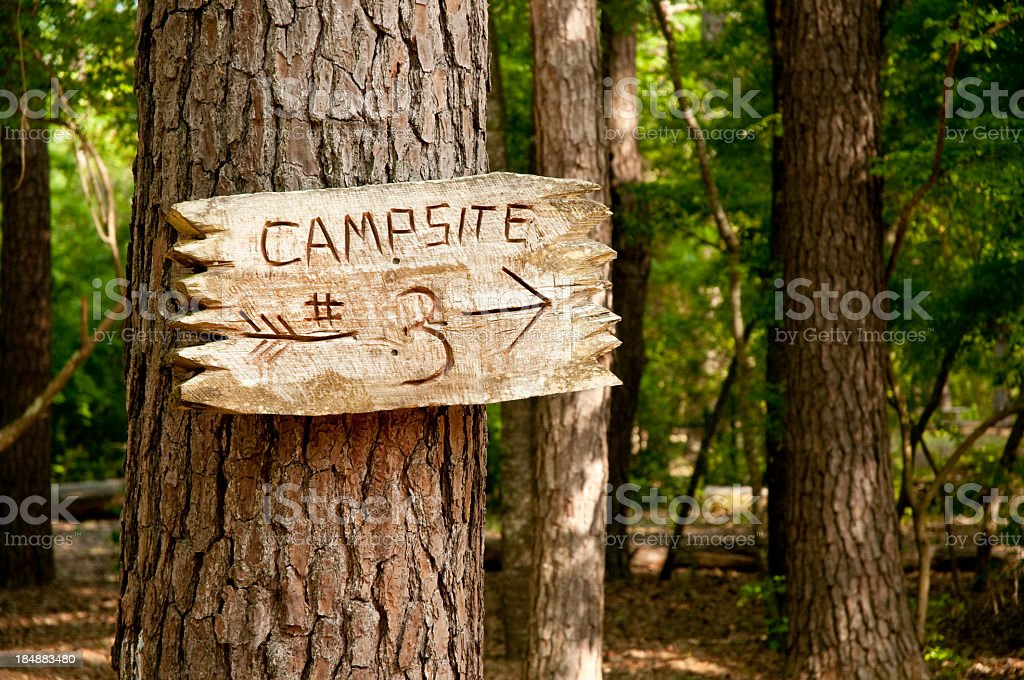 Tree trunk with wood sign and arrow to campsite 3 royalty-free stock photo