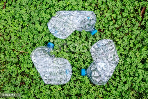 499093370 istock photo tree wasted plastic bottle in shape of the symbol of recycling on green background. 1199051116