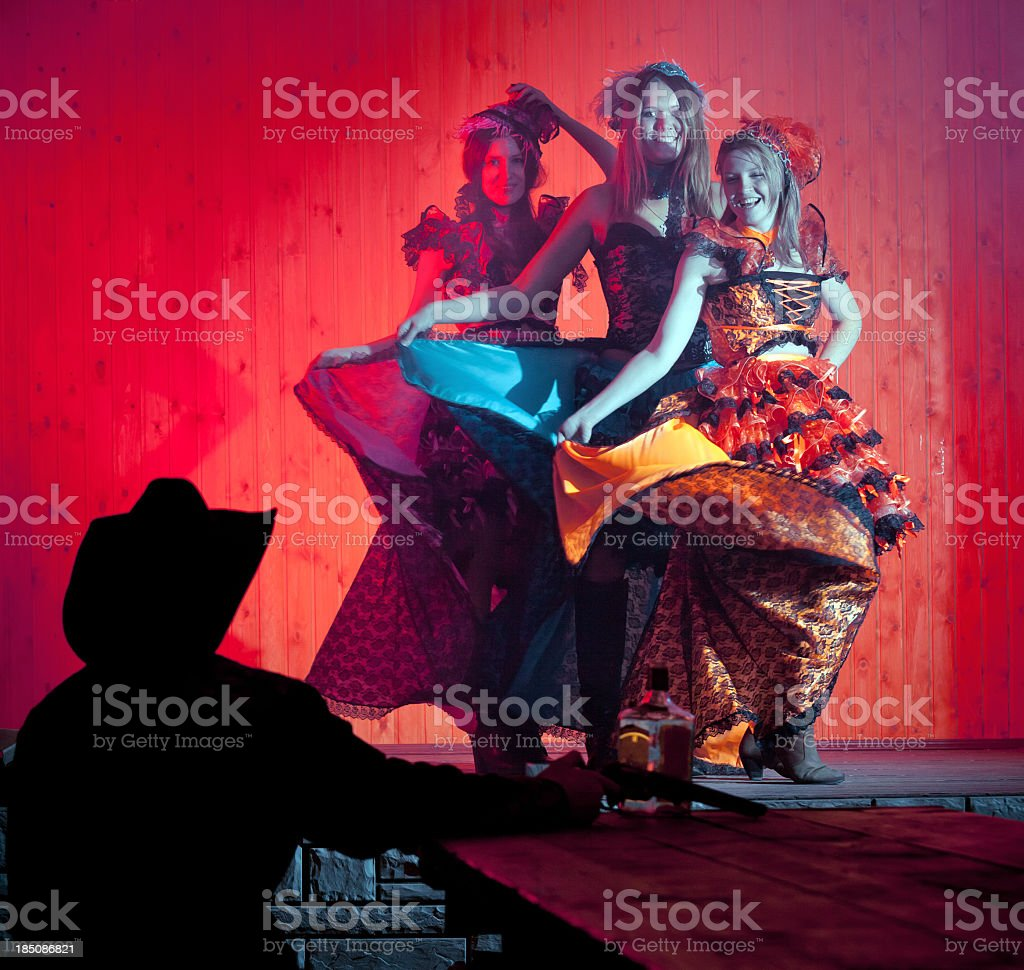 Tree young cancan dancers dancing before cowboy stock photo