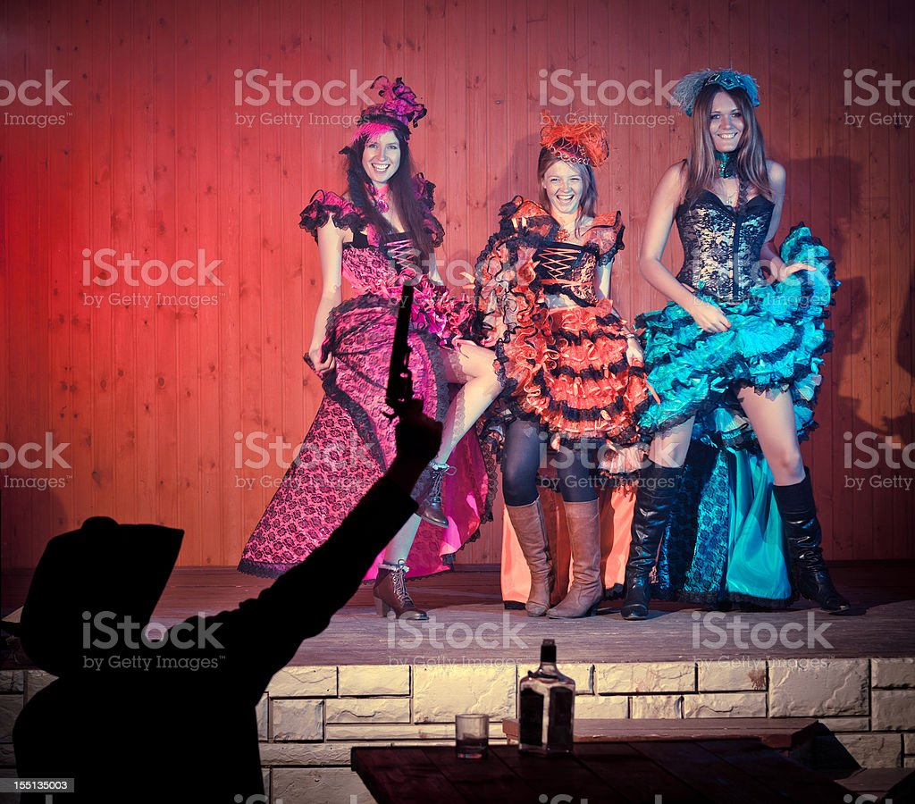 Tree young cancan dancers dancing before cowboy with gun stock photo