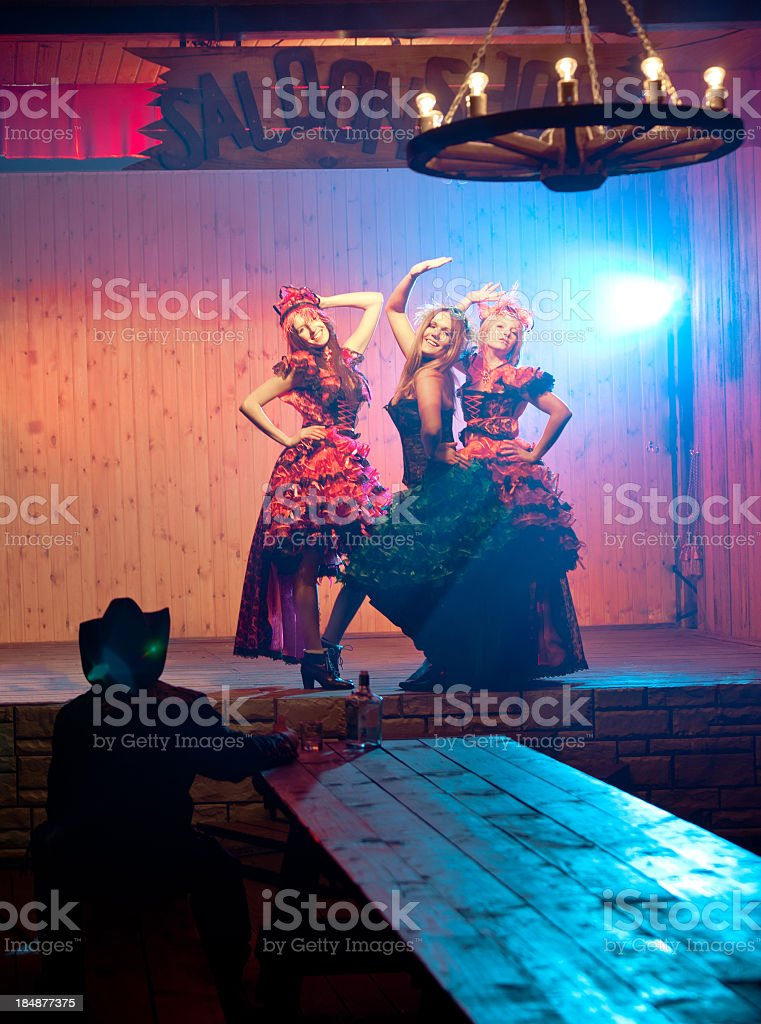 Tree young cancan woman dancing before cowboy at table stock photo