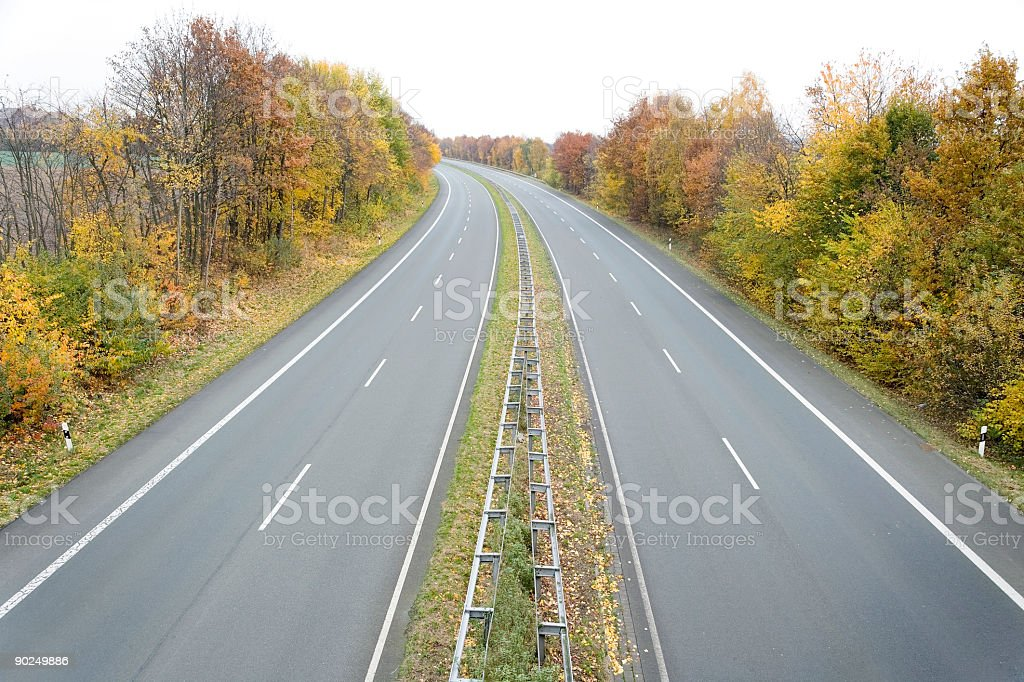 Treelined two lane highway in autumn (XXL) royalty-free stock photo