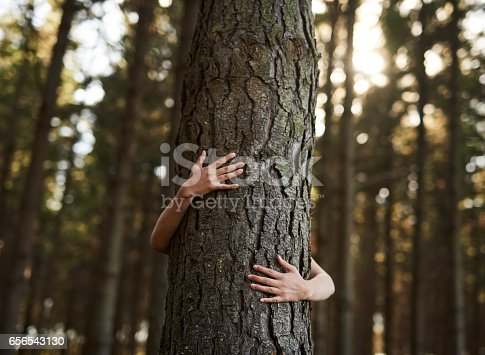 Shot of an unidentifiable young woman hugging a tree in the forest