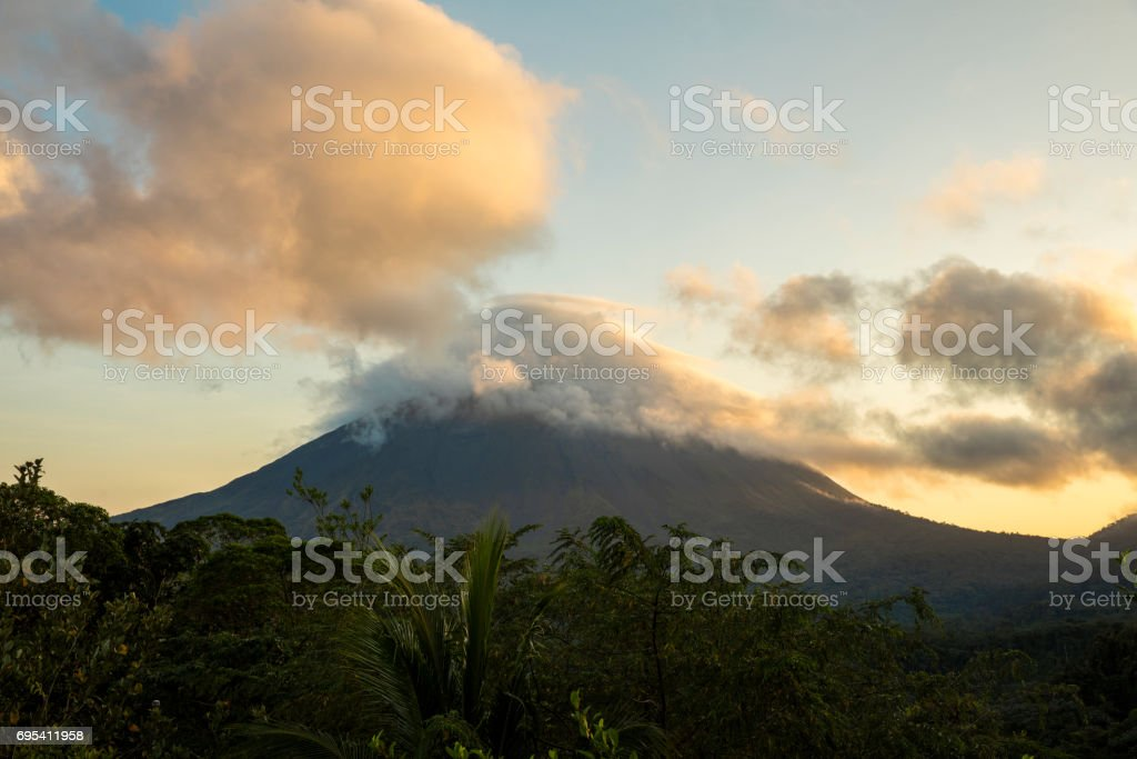 Trees growing against Arenal Volcano during sunset stock photo