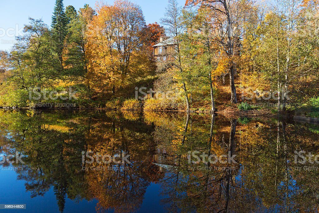 Trees in autumn colors on a lake with a house Lizenzfreies stock-foto
