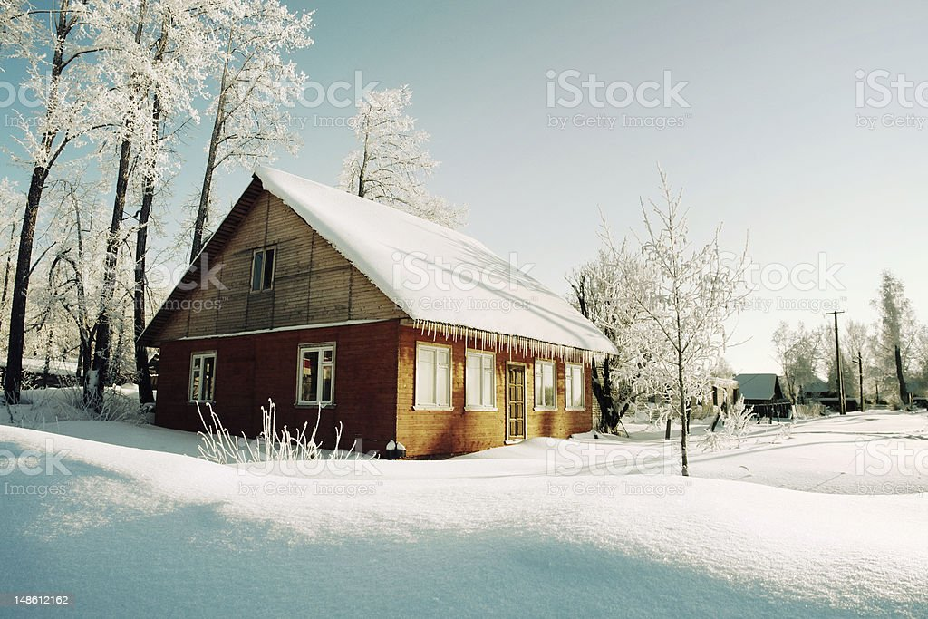 Trees in hoarfrost, red house of winter village stock photo