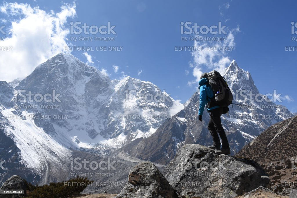Trekker on the Everest Base Camp Trek in front of Mount Cholache and Mount Tabuche stock photo