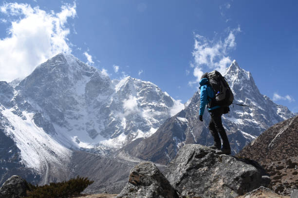 trekker on the everest base camp trek in front of mount cholache and mount tabuche - alpinismo foto e immagini stock