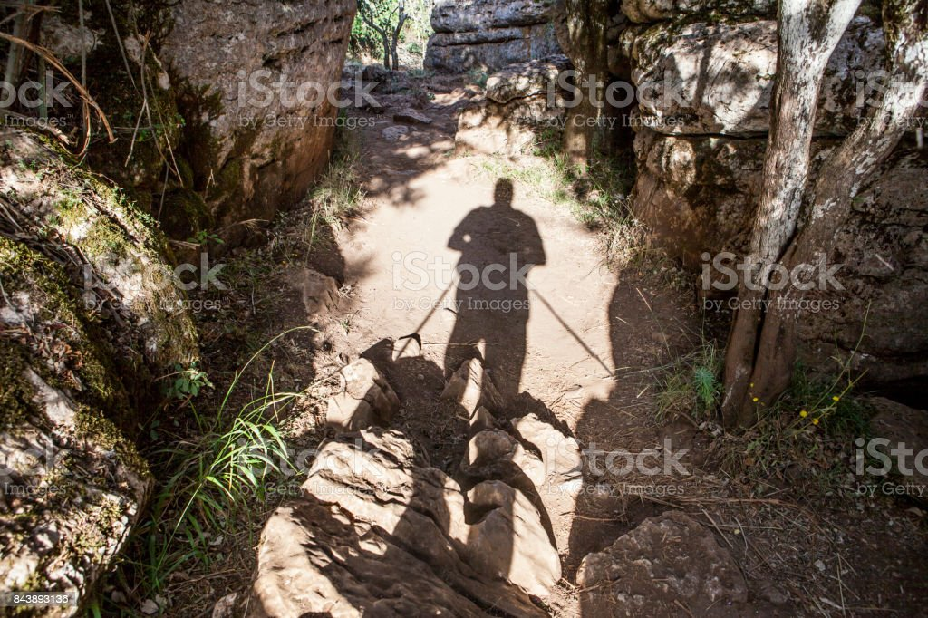 Trekker shadow walking by Torcal Natural Park trails, Spain stock photo