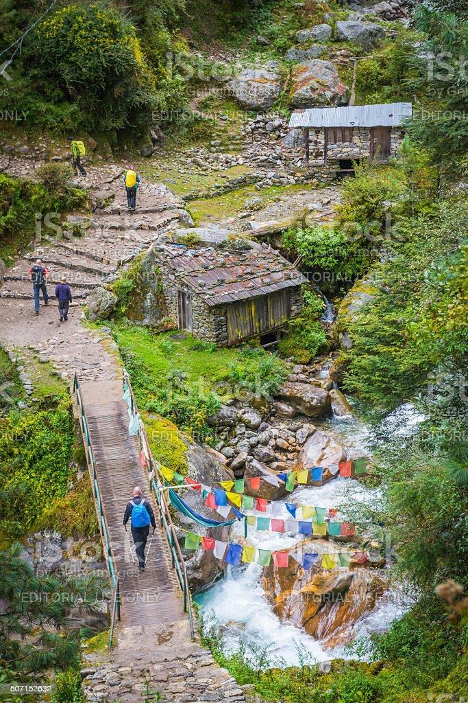 Trekkers hiking on Everest trail past prayer flags Himalayas Nepal stock photo