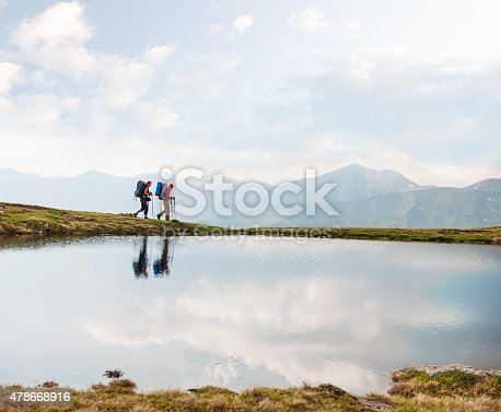 Two hikers passing by a calm mountain lake reflecting the sky