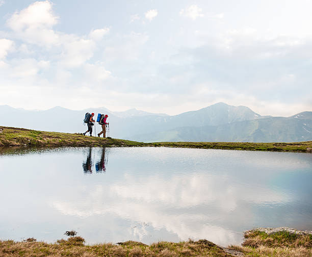 Wanderer vorbei an einem ruhigen See in den Bergen – Foto