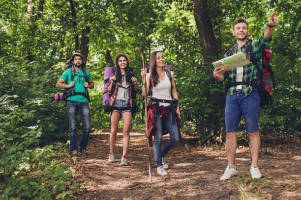 randonnée, le camping et le concept de la vie sauvage. les quatre meilleures amies sont randonnée dans les bois de printemps, le mec montre la direction, dame c'est de vérifier sur une carte, sont tous excités et anxieux - guide photos et images de collection