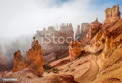 People trekking the Navajo loop trail in Bryce Canyon National Park at sunrise with some clouds and fog. Utah, USA