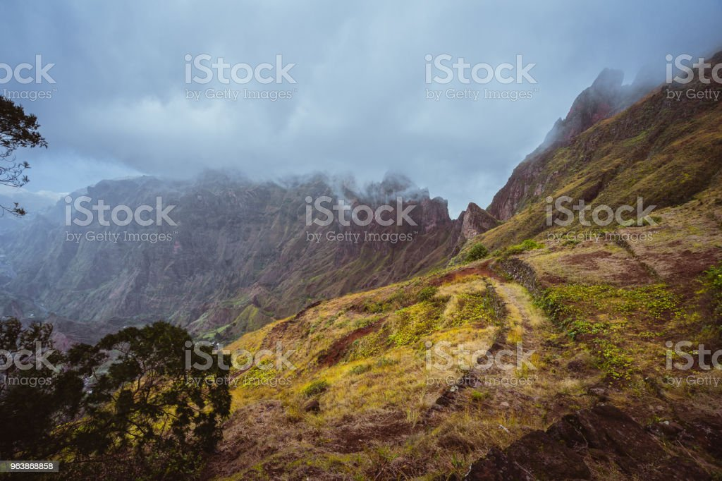 Trekking path along the mountain edge overgrown with verdant grass. Mountain peaks are covered by fog . Xo-Xo Valley. Santo Antao Island, Cape Verde Cabo Verde - Royalty-free Adventure Stock Photo