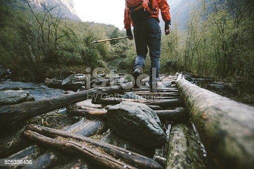 Cropped shot of mountain trekker crossing the bridge in region of Annapurna, Himalayas.