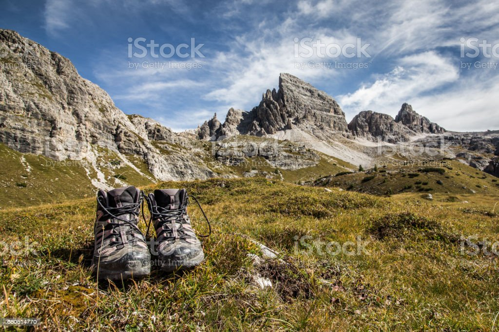 Trekking shoes (boots) on grass in front of stunning mountain scenery and blue skies clear weather. The mountain in the background is Monte Paterno, Parco naturale Tre Cime. stock photo