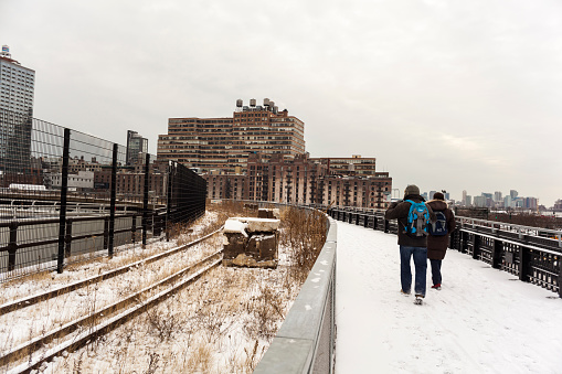 New York City, NY, USA - January 9, 2015: Tourists trek the snow covered High Line. Preserved rail track in section 3 of the High Line, left.  12th ave to the right.