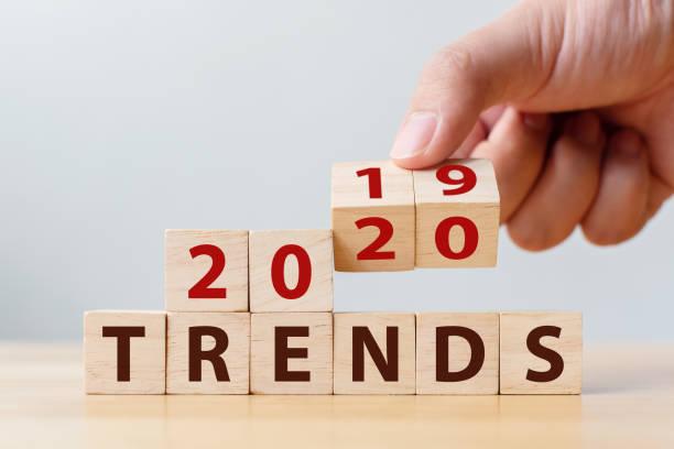 2020 trend concept. hand flip wood cube change year 2019 to 2020 - молодёжная культура стоковые фото и изображения