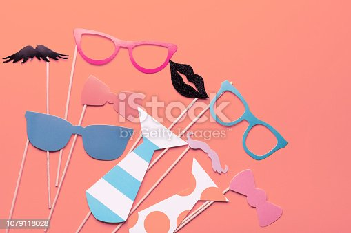 istock Trend photography on the theme of the new color of the year 2019 - Living Coral. Photo booth props glasses, mustache, lips on a pink background flat lay. Birthday parties and weddings. 1079118028